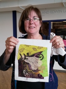 Art teacher showing her very artistic piece that she made in about 30 minutes, using heat activated fusing and fabrics.